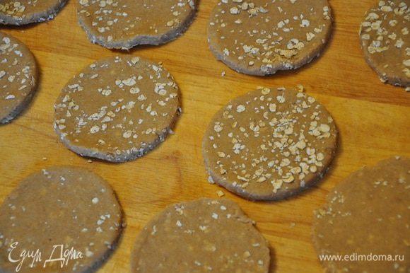Рабочую поверхность посыпать хлопьями и раскатать на них тесто в пласт толщиной 3 мм., вырезать круглой формочкой печенье, обрезки теста снова раскатывайте и снова вырезайте, так пока не останется теста.