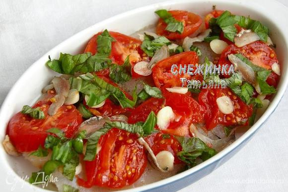 На рыбку в форму кладём кольца томатов, анчоусы, чеснок. Распределяем базилик.
