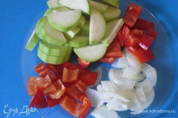 Для начинки овощи вымыть. Лук и кабачок очистить. У перца удалить сердцевину, крупно нарезать. Лук нарезать полукольцами, кабачки нарезать кружочками, а потом на 4 части.