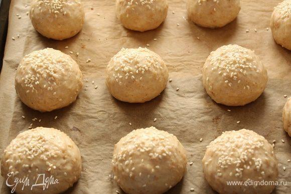 Противень покройте пекарской бумагой и уложите на него булочки. Намажьте булочки взбитым яйцом. Сверху посыпьте кунжутом. Поставьте противень в разогретую до 180-200 градусов духовку для выпечки на 30-35 минут.