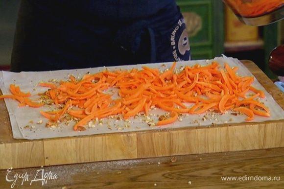 Посыпать тесто частью орехов со специями и равномерно разложить сверху натертую тыкву.