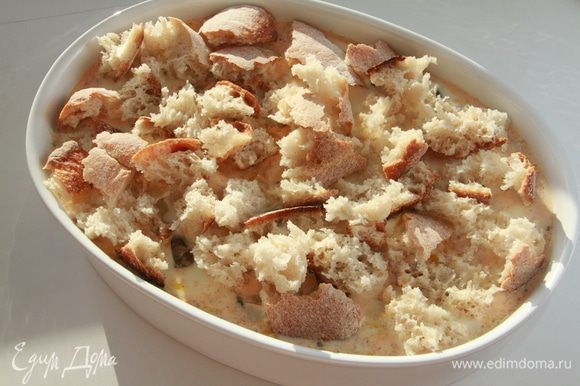 Багет поломать на кусочки, выложить поверх мяса с грибами, слегка придавить, чтобы хлеб погрузился в соус.