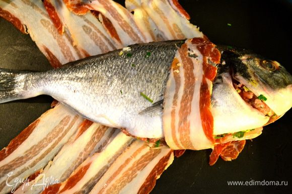 Положить рыбу в центр плетения из бекона и завернуть в него, чередуя бекон с левой и правой стороны.