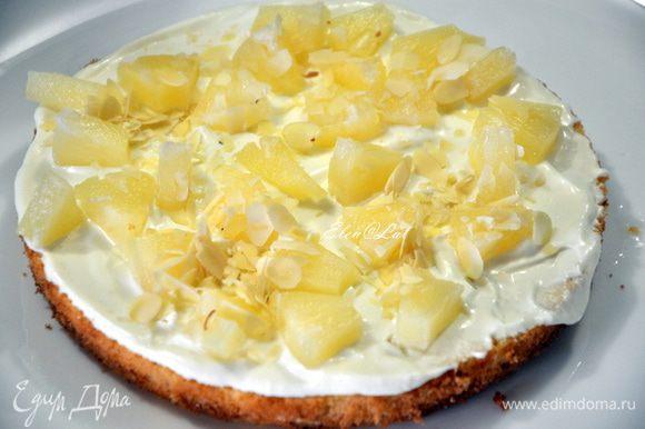 Сверху укладываем ананасы и обсыпаем миндалем (очень еще вкусно с грецкими орехами). Затем начинаем укладывать горкой кубики бисквита, и каждый слой также смазываем кремом, добавляем ананасы и миндаль.