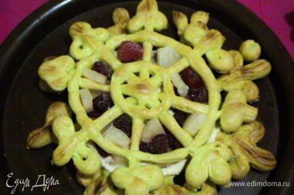 На блюдо выложить самую большую снежинку. Намазать кремом и выложить кусочки ананаса и малину. Сверху снежинку чуть меньшего диаметра, в промежутки выложить начинку из малины и ананаса и покрыть кремом и так до последней снежинки.