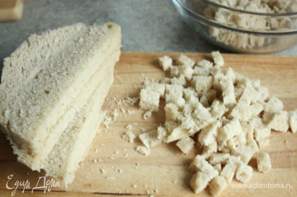 Растопить в сковороде 10 г сливочного масла, добавить бекон, затем 1/3 лука и слегка обжарить в течении 5 мин., остудить. Хлеб без корок порезать маленькими кубиками, положить в миску.