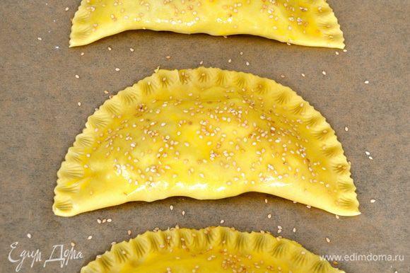 Украсить край каждого пирожка и выложить их на противень (у меня получилось два противня по три пирожка на каждом). Смазать пирожки оставшимся яйцом и присыпать кунжутными семенами. Выпекать в центре духовки 20 минут, пока тесто не покроется золотистой корочкой.