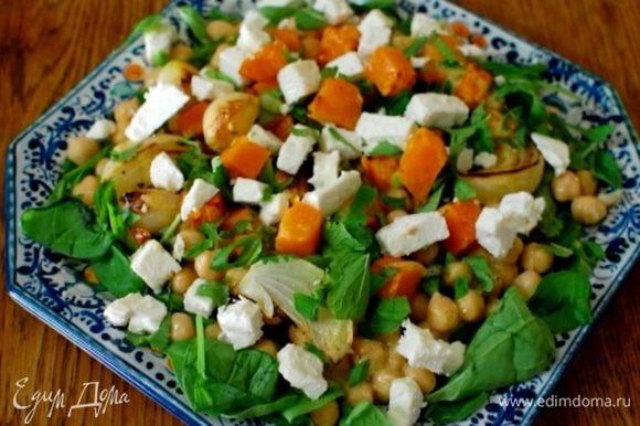 Выложить на тарелку шпинат, затем нут и запеченные овощи, полить оставшейся заправкой, посыпать измельченной зеленью, сверху разложить кусочки феты.