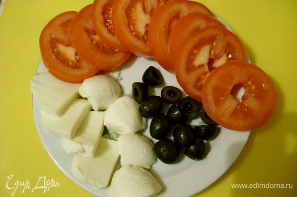Помидоры нарезать кружочками, маслины - пополам, моцареллу - толстыми ломтиками.