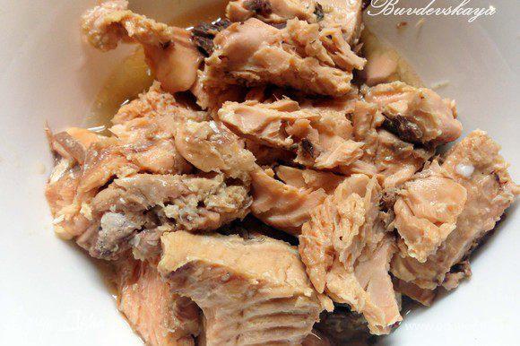 Открыть банку с рыбой, сок перелить в миску (НЕ ВЫЛИВАТЬ !) . Отделить рыбу от кожи и костей, переложить в миску с соком и размять вилкой. Выложить слой рыбы на белок, немного поперчить.