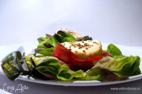 Достаём сыр из духовки, перчим, выкладываем на салат или рядом с салатом. Кунжут, который хорошенько просушился, распределяем по салату. Подаём с багетом, например, ячменным или из полбы. Всё разнообразие.