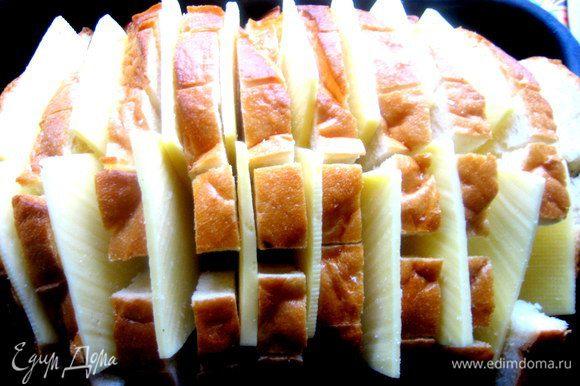 Помещаем хлеб в смазанную форму,раздвигаем слегка куски и всовываем по два кусочка сыра между ломтями.
