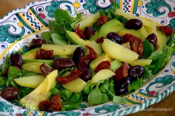 На салат с авокадо выложить картофель, маслины и вяленые помидоры.