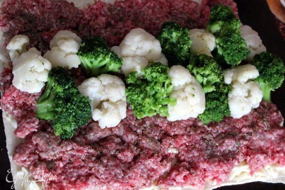 Брокколи и цветная капуста могут быть свежими или замороженными, если свежие, то желательно предварительно отварить. Распределите мясной фарш тонким равномерным слоем на тесте и посыпьте его морской солью и сухими итальянскими травами с паприкой. По центру разложите соцветия брокколи и цветной капусты, чередуя их в шахматном порядке.