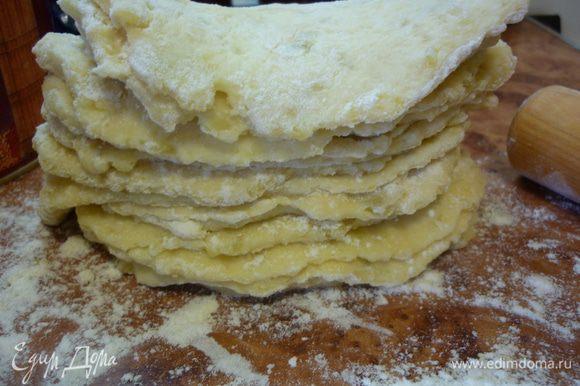 От теста отламываем кусочки размером с грецкий орех, на хорошо посыпанном мукой столе раскатываем лепешки толщиной полсантиметра и складываем их друг на друга. У меня получилось 19 штук.