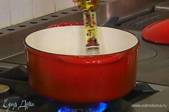 Разогреть в тяжелой кастрюле растительное масло.
