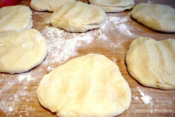 На хорошо присыпанной мукой поверхности скатываем тесто в багет и делим его на 9 равных частей, каждую часть немного разминаем руками в лепешку.