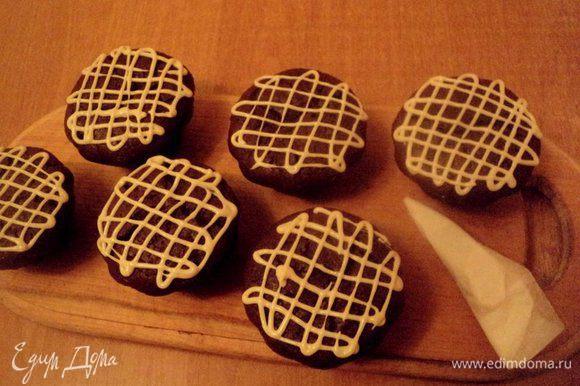 Готовые маффины охладить и украсить сеточкой из белого шоколада. Белый шоколад предварительно растопить вместе со сливками в микроволновке или на водяной бане. Украшать с помощью корнетика из бумаги для выпечки.