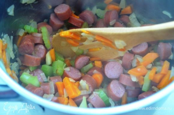 Добавить сосиски, Перемешать и жарить на среднем огне еще 5 минут.