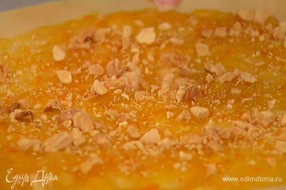Половину теста раскатать в тонкий пласт и выложить на бумагу для выпечки, затем, отступая на 2 см от края пласта, смазать апельсиновым джемом и посыпать измельченными орехами.