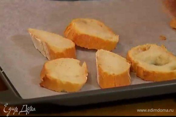Багет нарезать кусочками и выложить на противень, выстеленный пекарской бумагой.