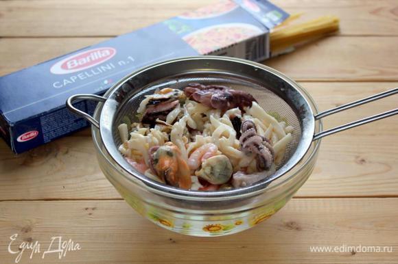 С морского коктейля из ассорти морепродуктов слейте лишнее масло.