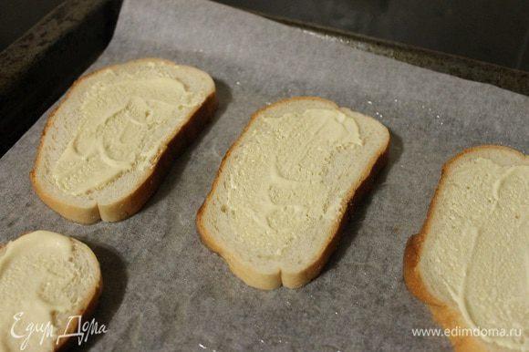 Застилаем противень пергаментом, смазываем маслом, выкладываем 4 ломтика хлеба, смазываем их соусом.