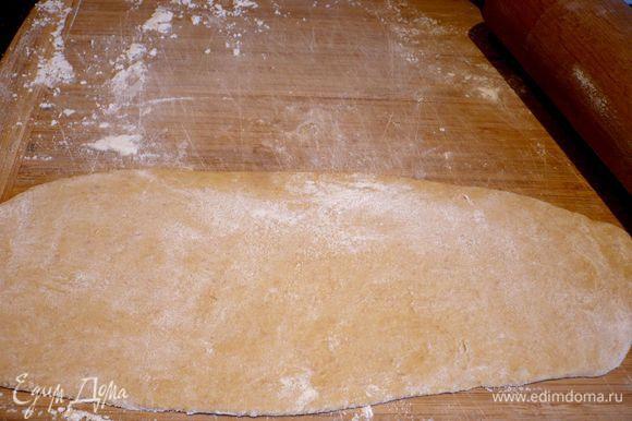 Присыпаем тесто сверху мукой, хорошо подпыляем доску и начинаем раскатывать тесто в удлиненный пласт, двигая скалку только вверх и вниз, пока толщина теста не достигнет максимум нескольких миллиметров.