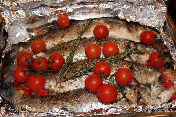 Запечь рыбу в разогретой до 200 градусов духовке в течение 15 минут. Затем достать, выложить на рыбу веточку розмарина и помидоры. Запекать еще 10 минут.