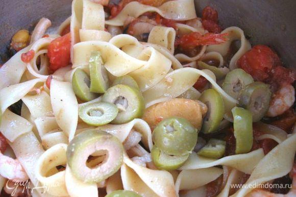 Оливки порезать кусочками. Добавить к морепродуктам пасту, оливки, измельченный базилик.