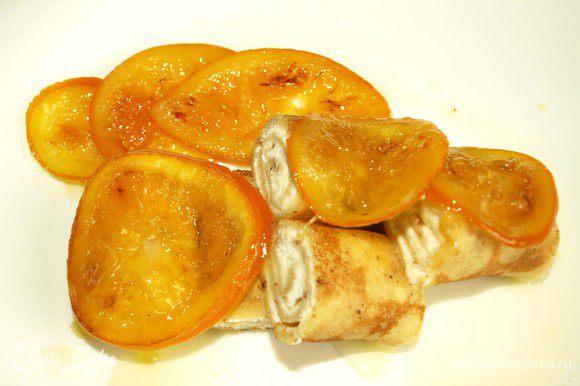 Достать из холодильника блины, нарезать их кусочками, выложить на тарелку. Полить апельсиновым сиропом и сверху выложить карамелизированные апельсины.
