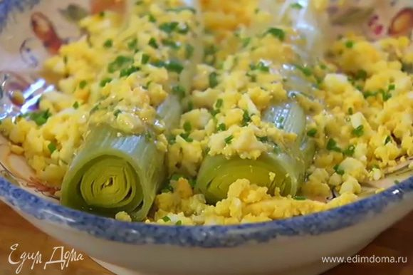Запеченный лук-порей выложить в глубокую тарелку, полить заправкой, посыпать оставшимся яйцом и шнитт-луком.
