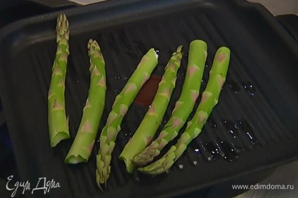 Разогреть в сковороде-гриль оливковое масло и обжарить спаржу с двух сторон, затем снять со сковороды.
