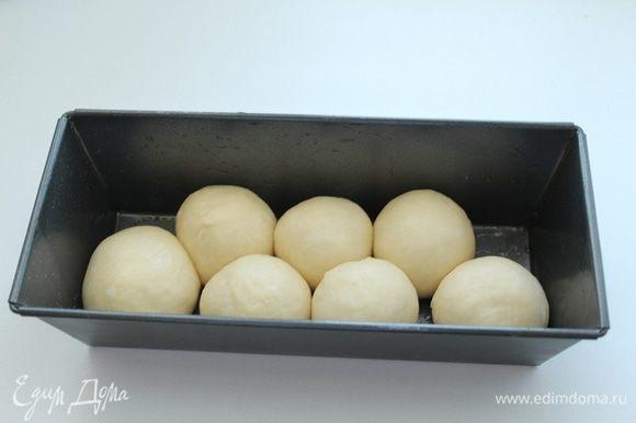 Когда тесто увеличится вдвое, обмять его и разделить на 16-20 шариков. Смазанными растительным маслом руками,выложить в смазанную маслом форму для выпечки половину шариков.