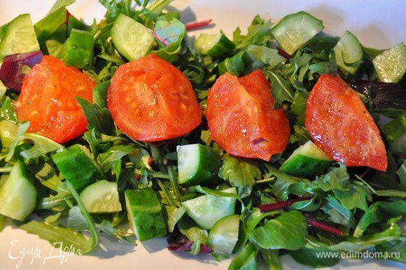 На тарелку выложить зелень, затем порезанный крупными кубиками огурец. Выложить помидоры и все посолить.