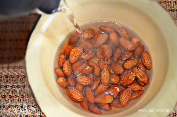 Миндальные орехи залить кипятком, дать постоять 5 мин, затем очистить их от шелухи.
