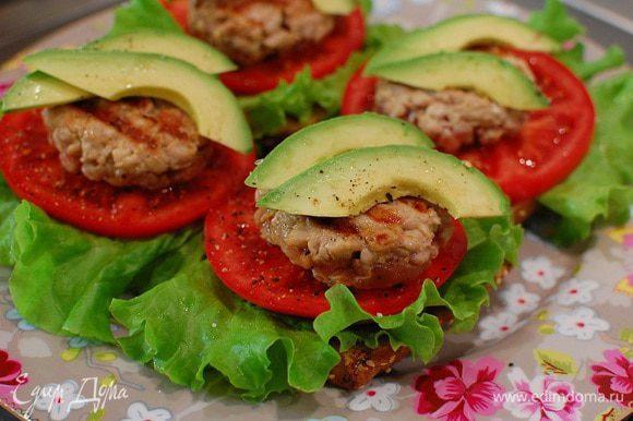 На каждую половинку булочки выложить лист салата, кружок помидора, котлетку и пару кусочков авокадо.