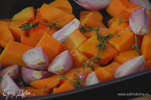 Нарезанную тыкву выложить в небольшой глубокий противень, посыпать листьями тимьяна, сбрызнуть оливковым маслом, добавить шалот, посолить, поперчить и слегка встряхнуть.