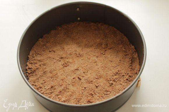 На бумагу для выпечки в разъемную форму диаметром 20 см выложите 2/3 крошки и слегка прижмите.