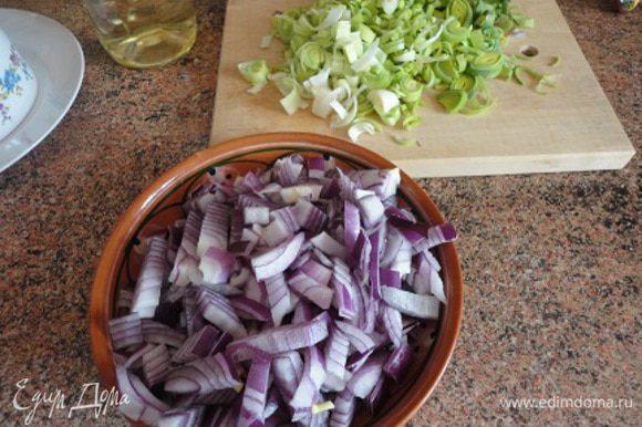 Красный лук мелко нарезать. Так же нарезать лук порей вместе с зеленой частью (можно и без лука порея). В сковороде или кастрюле с толстым дном разогреть растительное масло вместе с оливковым, выложить красный лук и лук порей и жарить на медленном огне постоянно помешивая 25 минут, пока лук не станет золотистым и начнет карамелизоваться.