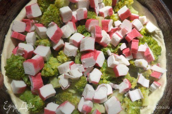 На пласт теста выложить остывшую брокколи, крабовые палочки. Залить всё яично - молочно - сливочной заливкой.