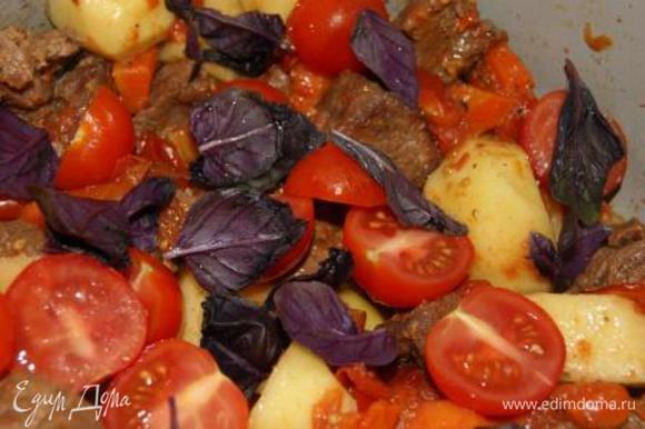 Добавить картофель, черри и листья базилика к мясу, готовить на среднем огне еще 20 минут
