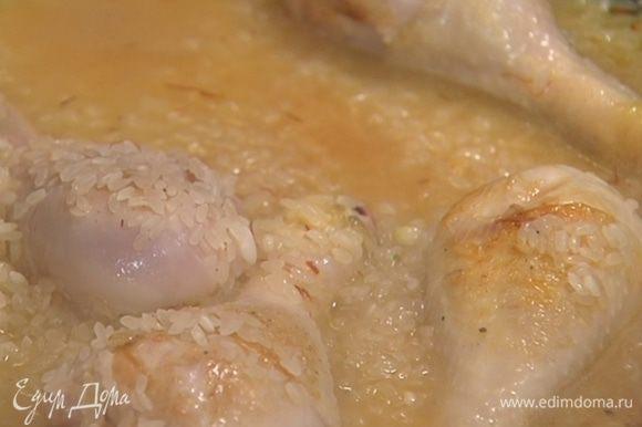 Всыпать рис, влить горячий бульон, так чтобы рис был покрыт, добавить шафран, паприку и накрыть крышкой.
