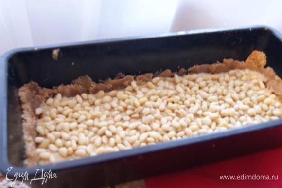 Выложить крем, посыпать кедровыми орешками.