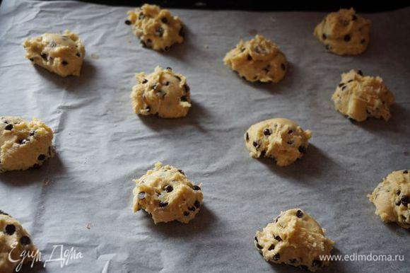Добавляем шоколадные термостабильные капли, перемешиваем. С помощью столовой ложки выкладываем печенье на противень, застеленный пекарской бумагой.