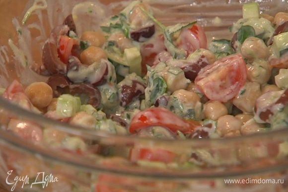 Готовый нут, огурец, помидоры, сельдерей и оливки выложить в салатницу, добавить мяту, базилик и заправку, все перемешать.