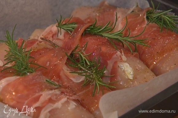 Небольшой глубокий противень выстелить пищевой бумагой, выложить фаршированные грудки плотно друг к другу, сбрызнуть оливковым маслом, посолить и поперчить.