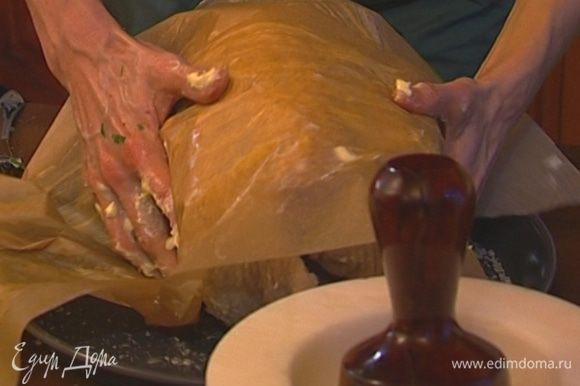 Обернуть индейку бумагой и уложить на противень. Влить в противень 250 мл теплой воды.