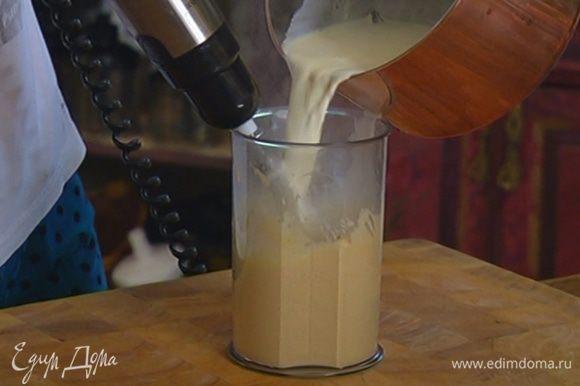 Продолжая взбивать, тонкой струйкой влить горячие сливки с молоком и взбить еще немного.