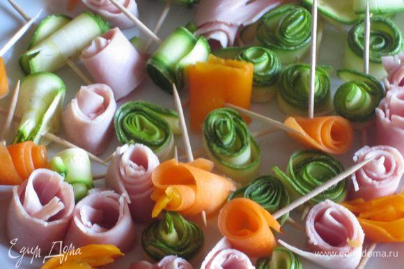 Овощи: цукини нарезать тонкими ломтиками с помощью овощечистки. Свернуть розочкой и скрепить зубочисткой. Из тонко нарезанной ветчины тоже сделать розочки и скрепить зубочисткой. Морковь отварить до полуготовности в кипящей воде, очистить овощечисткой, нарезать тонкими ломтиками, свернуть розочками и скрепить зубочистками. Каждый цветочек подрезать, чтобы они были одинаковой высоты.